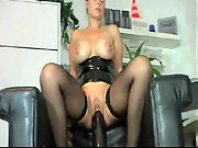 Perfect platinum-blonde riding a giant dark-hued dildo